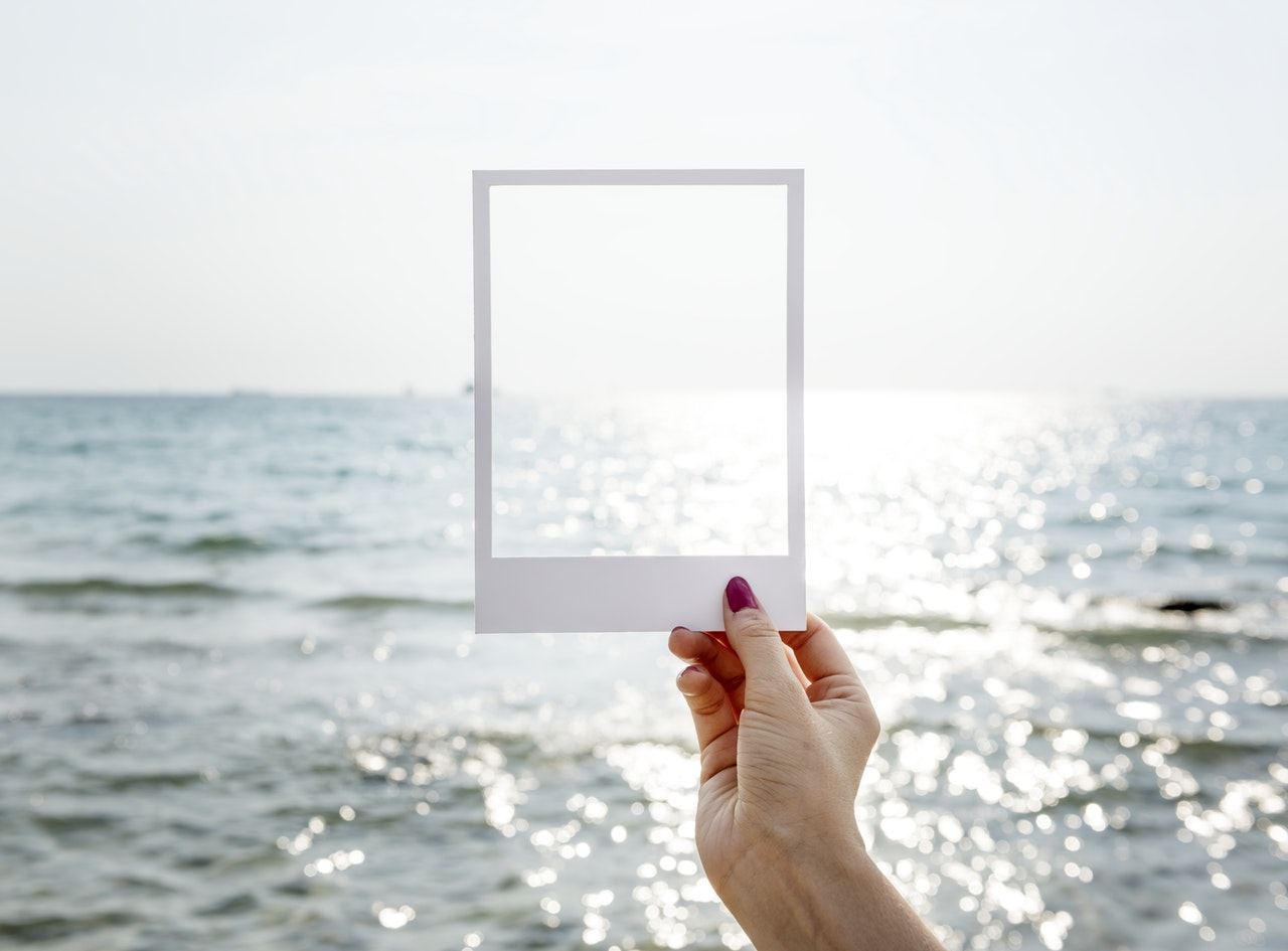 Person holding frame out towards ocean